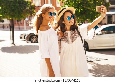 Two young female smiling hippie brunette and blond women models in summer white hipster dress taking selfie photos for social media on smartphone on the street background. Surprise face, emotions