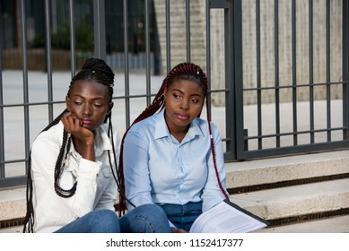 two young female students with documents sitting on stairs in the city and thinking