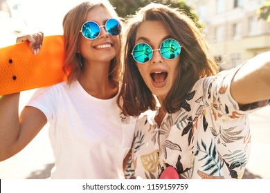 Two young female stylish hippie brunette and blond women models in hipster clothes taking selfie photos for social media on smartphone on the street background. With colorful penny skateboards