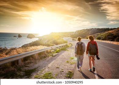 Two young female travel girlfriends walking along a highway, against a background of sunset and sea coast. Travel and freedom, adventures and directions for travel