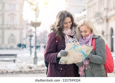 Two young female traveler standing on the street and looking at the map