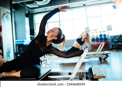 Two young females wearing sports clothing doing reformer exercises on pilates machines indoors in a studio