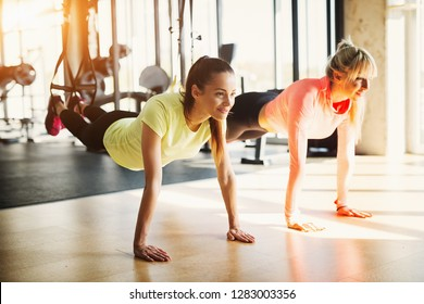 Two young fit girls in a gym doing TRX suspension training.