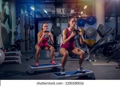 Two young fit girls working out in a gym. Standing on stepper and doing squats while holding weights in hands.