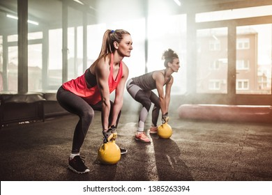 Two young fit woman working out with a kettle bell in the gym