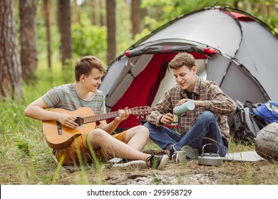 Two young friend sitting in the tent, play the guitar and sing songs