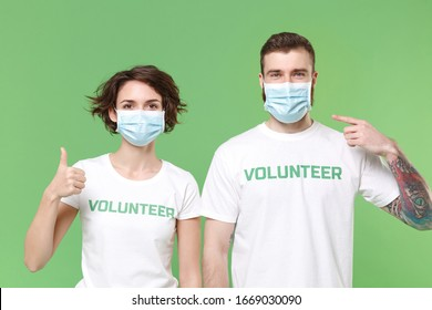 Two young friends couple in volunteer t-shirt isolated on pastel green background. Voluntary free work assistance help charity grace teamwork. Point index finger on sterile face mask showing thumb up