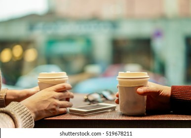 Two young friends drinking coffee in paper take away cup - People having a break sitting in bar restaurant toasting cappuccino - Winter concept - Focus on man hand - Soft saturated retro filter