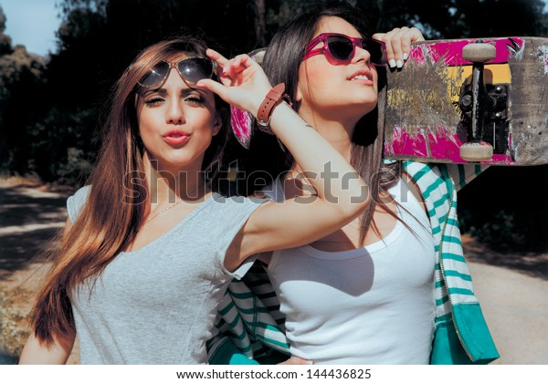 two young friends holding a skateboard and sending a kisses . Summer style pictures.