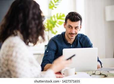 Two young friends with laptop indoors, house sharing concept.