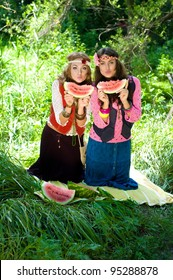 Two young funny girls hippie eat a water-melon on a lawn