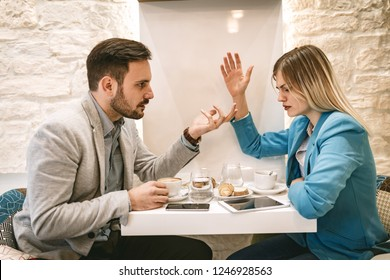 Two young furious businesspeople pick a quarrel at cafe.