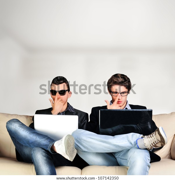 Two young gamers sitting together on sofa and using their laptops