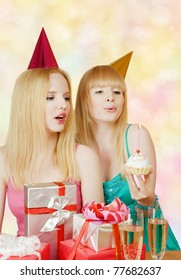Two young girl at birthday party with gift box and cake