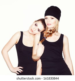 Two young girl friends standing together. Brunette put her head on the blonde's shoulder, looking at camera. Inside