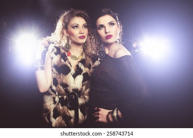 Two young girl friends standing together and having fun. Looking at camera. Inside club fashion vintage style
