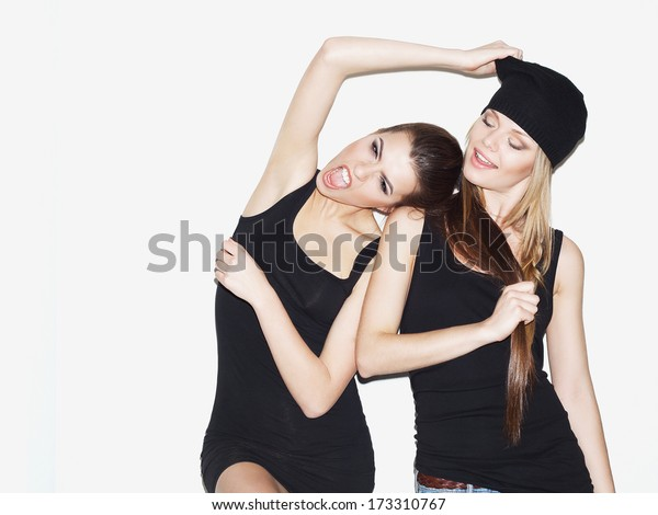 Two young girl friends standing together and having fun. Brunette pulling blonde's beanie and laughing. Blonde keeping brunette's hair (ponytail) and smiling. Casual style. Inside.