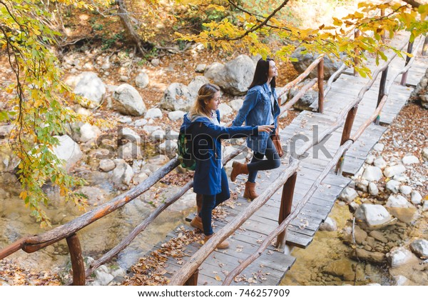 Two young girl friends walking together in autumn forest. Girlfriends standing on a bridge over the river and admiring nature.