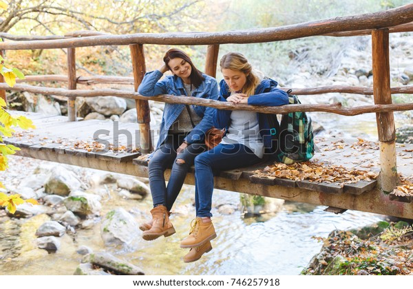 Two young girl friends walking together in autumn forest. Girlfriends sitting on a bridge over the river.