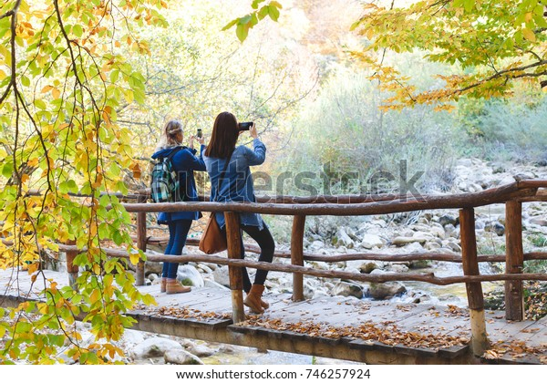 Two young girl friends walking together in autumn forest. Girlfriends standing on a bridge over the river and taking pictures of the nature on smartphone.