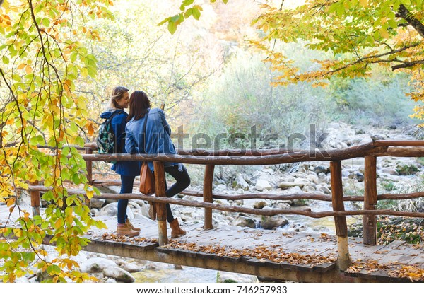 Two young girl friends walking together in autumn forest. Girlfriends standing on a bridge over the river and talking to each other.