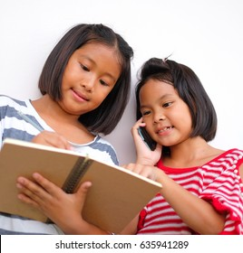 Two young girl holding a brown notebook and pencil in hands. Thai student learning together and calling smartphone.
