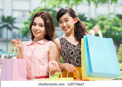 Two young girlfriends with shopping bags looking at camera