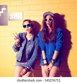 Two young girlfriends in sunglasses having fun. Lifestyle