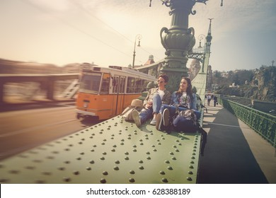 Two young girlfriends traveling, sitting on a bridge, enjoying the sunny day and the sightseeing of the city