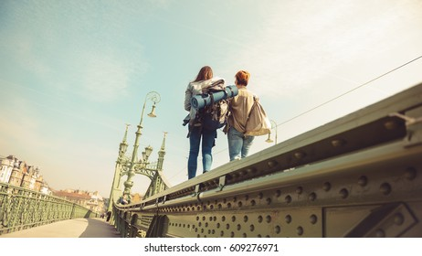 Two young girlfriends traveling, walking on a bridge, enjoying the sunny day and the sightseeing of the city