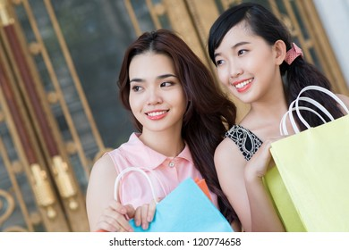 Two young girls with bags looking away