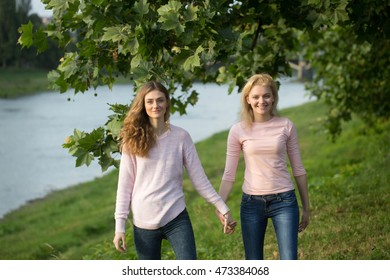 Two young girls best friends hold hands walking along river on summer day in green park