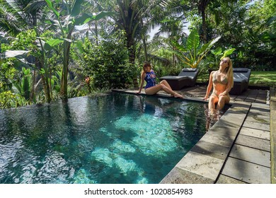 Two young girls are blond and red, sitting on the edge of the infinity pool in the jungle. Taken on the island of Bali in Ubud.