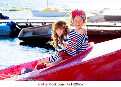 two young girls with the boat, looking around and smiling