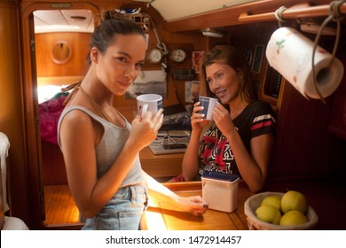 two young girls chat and joke among themselves, having breakfast in the galley of a sailing boat