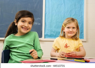 Two young girls in classroom with art and drawing materials.