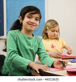 Two young girls in classroom creating art. Square format.