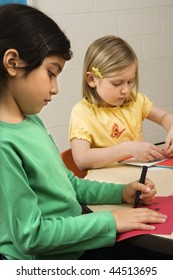 Two young girls in classroom creating art. Vertical shot.