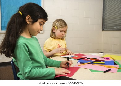 Two young girls in classroom creating art. Horizontally framed shot.