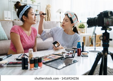 two young girls doing video recording by professional camera. asian woman make up artist applying powder on female blogger face with cosmetic products table in living room. beauty ladies live stream