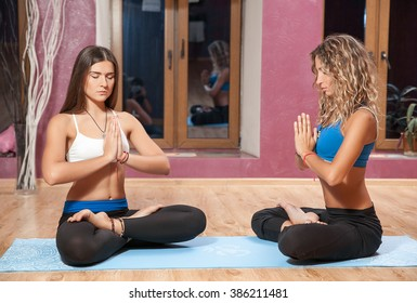 two young girls doing yoga in lotus position on mat
