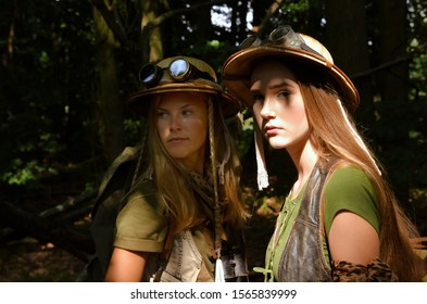 Two young girls dress up as explorers. They wears safari hats and wears khaki clothing. They are seen in a forest environment.