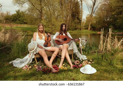 Two young girls dressed in vintage white clothes  sit in an aging wicker chair by a pond. Both girls show off a carefree and lazy attitude to playing  their musical instruments.
