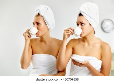 Two young girls drinking tea after sauna