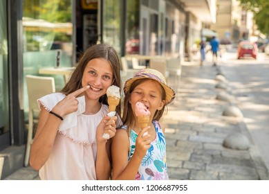Two young girls eating ice cream on side walk on coast on holiday.