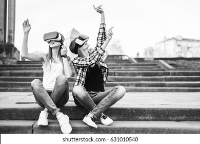 Two young girls enjoy virtual reality glasses outdoor, black and white