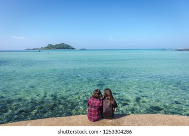 Two young girls enjoying the amazing blue water color sea of Jeju in South Korea