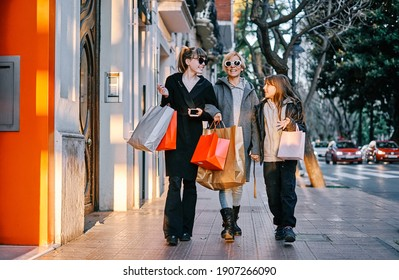 Two young girls and a girl walk along the sidewalk of a shopping street with shopping bags