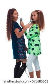 Two young girls girlfriends with long hair singing into two microphones on a white background