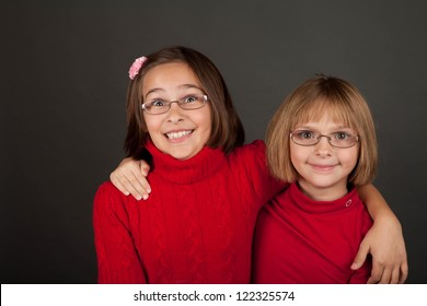 Two young girls with glasses in a bright red sweater